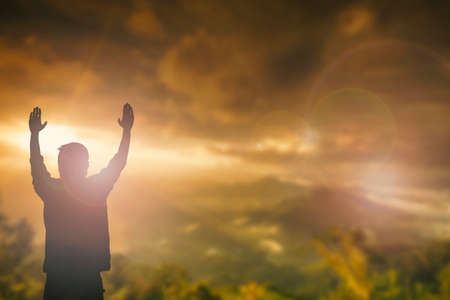 worship god: Silhouette of man with raised hands over blur cross concept for religion, worship, prayer and praise.