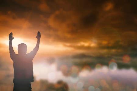 Het silhouet van de mens met opgeheven overhandigt onduidelijk beeld dwarsconcept voor godsdienst, verering, gebed en lof.