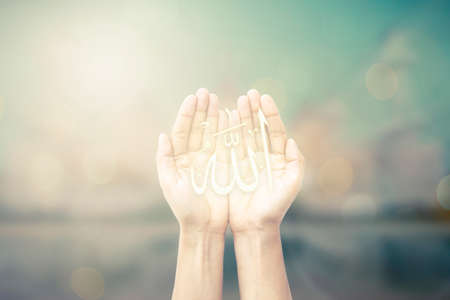 islamic scenery: Human hands pray and mosque background.
