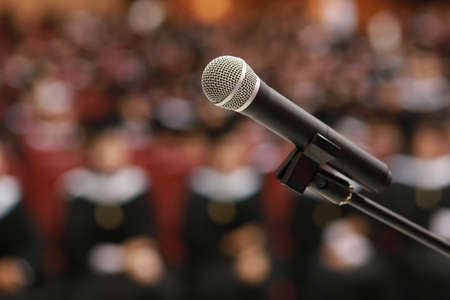 vdo: Wireless microphone on stage in auditorium with graduate student background
