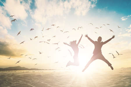 Silhouette of couple generation jump on beautiful background.