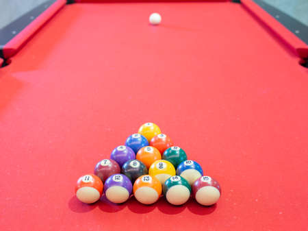 Billiard ball on red table background in pub bar room concept for sport gamble activity, game play competition. Stock Photo