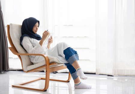 Jeunes femmes musulmanes Les étudiantes sont une journaliste indépendante créative qui écrit pour être un concept d'emploi d'entrepreneur pour une fille hijab Islam religion Asiatique ethnique joyeuse banque Internet sur tablette smartphone mobile Banque d'images