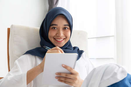 Young Muslim women Students is a creative freelance journalist sit writing to be entrepreneur job concept for hijab girl Islam religion Asian ethnic joyful internet banking on tablet mobile smartphone
