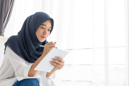 Young Muslim women Students is a creative freelance journalist sit writing to be entrepreneur job concept for hijab girl Islam religion Asian ethnic joyful internet banking on tablet mobile smartphone Stock fotó