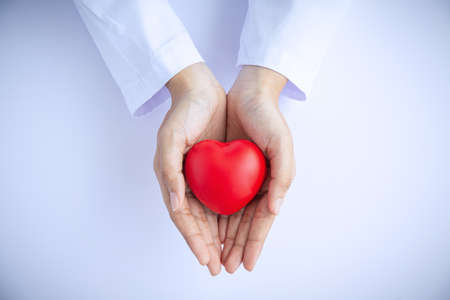 Woman doctor hands holding red heart on white background donate for hospital care concept. world heart day and world health day, CSR community, foster support patient.