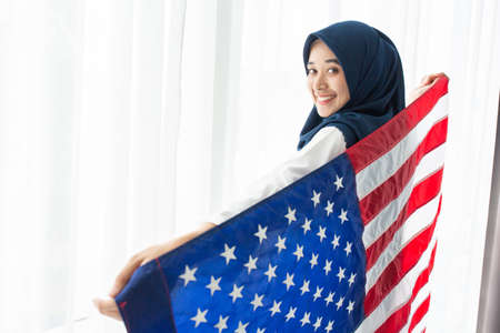 Young Muslim women exchange Students scholarship wear holding america flag over white background concept for hijab girl Islam religion Asian happy in united stage independent day culture