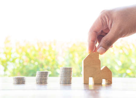 Money saving coins stack with growing interest in the public park on wood table concept for Wooden home model property investment mortgage financial real. Salary income for estate business dept.