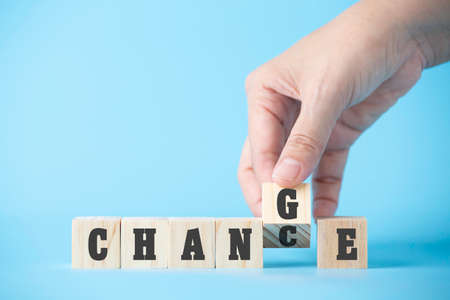 Woman hand hold wooden cube word on business blue background concept for change mindset to building organisation growth in success, chance of solution strategy opportunity, creative innovation management