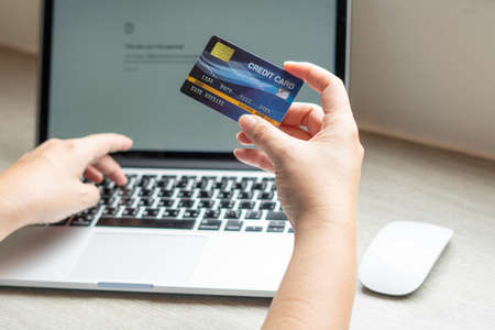 Business woman hand hold credit card to shopping internet online bill on computer, Debit saving purchase buy on table background. Shopaholic people retail pay sale money, bank terminal account concept