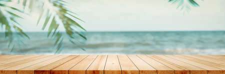 Panoramic empty clean wood counter table top blur shinny white bokeh light on summer beach background for product morning scene display montage, Abstract Blurry wooden desk in vacation trip backdrop.