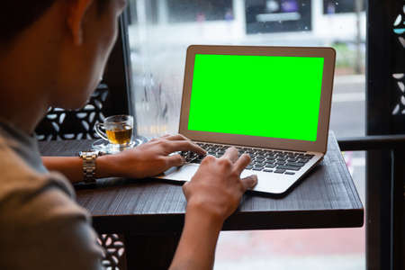 Young entrepreneur SME use notebook showing blank screen with clipping path display  in cafe concept. Hand of business man hold smartphone People use 5G cellular work app with modern internet of things