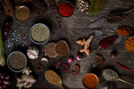 Condiment of indian food Spice garnish background on wood table top view. Seasoning of Asian organic herb cuisine flavour in kitchen board, chilli spicy taste concept 版權商用圖片