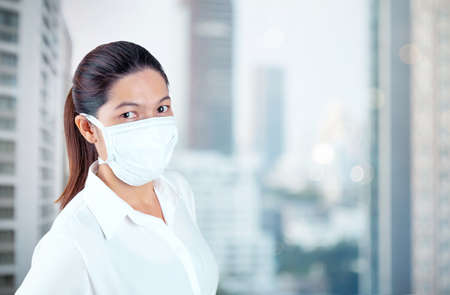 Young woman in safety medical mask in home isolation on blur outside office window view self business quarantine concept 版權商用圖片