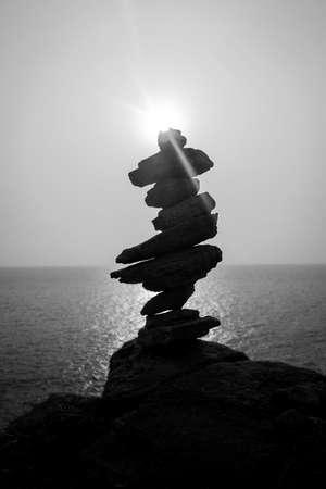 balanced: black and white sun set with  Balanced stones on the sea beach Stock Photo