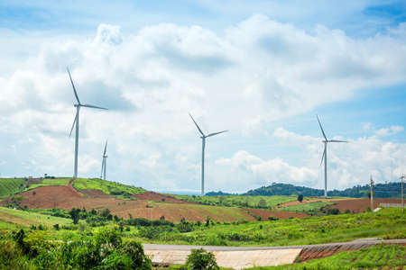 Windmills new energy with spring flower on the moutain at Khao Kho, Phetchabun, Thailand Stock Photo