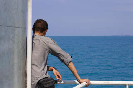 freedom of thought: lonely guy aboard the ferry stands and looks into the distance