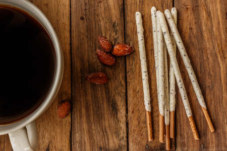 complement: Crispy sticks with white chocolate and almonds complement delicious coffee