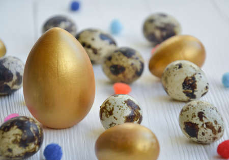 Easter. Easter eggs chicken and quail gold and natural color on a white wooden background with space for text.
