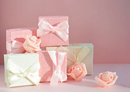 Boxes for small gifts in pastel colors and rosebuds on a light background with place for text. Advertising, poster.