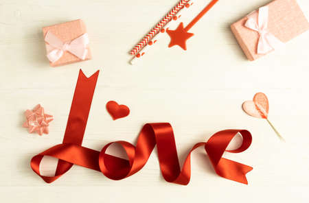 The word Love is written with a red ribbon on a white wooden background and boxes for gifts with space for text. Postcard template for the holiday.