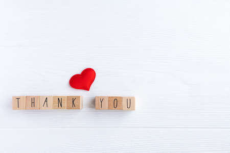 The word thank you on wooden cubes and a red heart on a light background with space for your text.