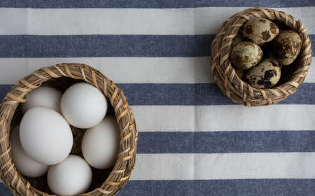White chicken, quail eggs in baskets and a towel on a white wooden background with space for text. Easter, holiday.