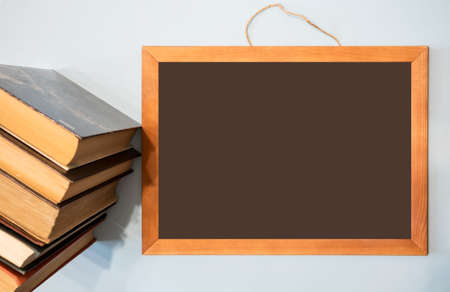 Chalkboard for your text and a stack of books. Distance education concept, course announcement.