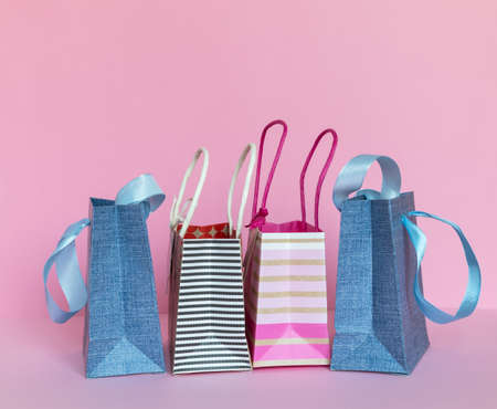 Colorful paper shopping bags on pink background.