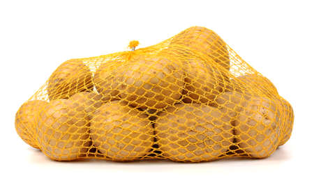 potatos: Heap of yellow raw potatos in red string bag. Isolated on white background. Close-up. Studio photography. Stock Photo