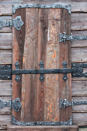 rustiness: Old wooden door with metal hinges and lock