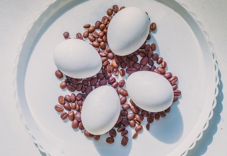 Coffee beans and Easter eggs, dyed with coffee on a background of burlap