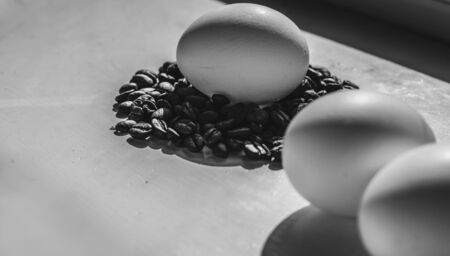 Coffee beans and Easter eggs, dyed with coffee on a background of burlap. Black and white style.