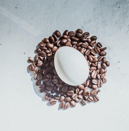 Coffee beans and Easter egg, dyed with coffee on a background of burlap