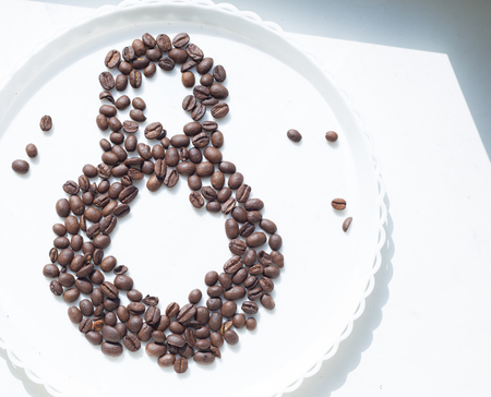 Coffee beans in form of number 8 and orchids on white plastic plate. International womens day. 8th march