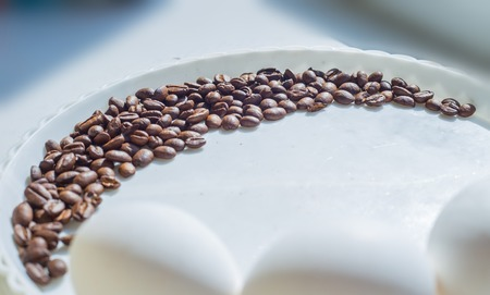 white fabric texture: Coffee beans in moon shape on white plate