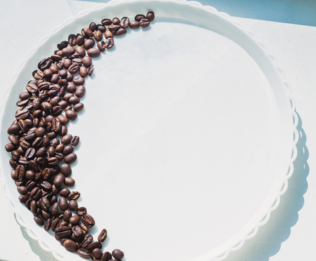Coffee beans in moon shape on white plate