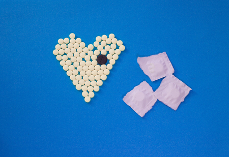 Yellow pills in shape of heart with the big black tablet on blue background Stock Photo