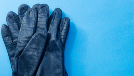Two leather gloves from above on blue background.
