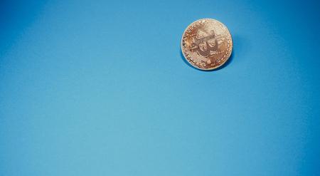 Cryptocurrency fysieke gouden bitcoin munt. Bitcoin, gouden bitcoin, gele bitcoin op blauw papier achtergrond