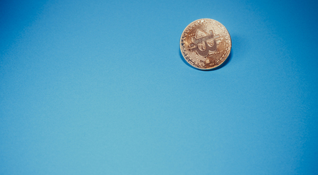 Cryptocurrency physical golden bitcoin coin. Bitcoin, golden bitcoin, yellow bitcoin in blue paper background