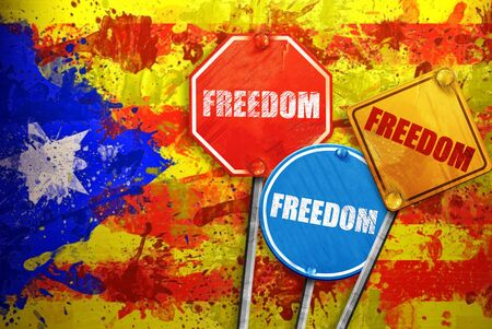 Political slogan in the form of traffic signs with Flag of Catalonia on the background. Signs with word FREEDOM. Independence of catalonia. Referernundum and protests in Catalonia, Barcelona. Stock Photo