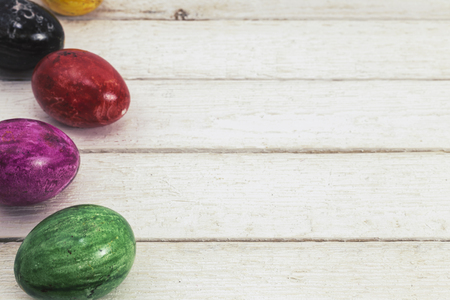 Colored easter eggs on white wood background. View from above. Copy space for text.