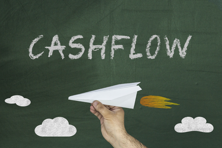 Hand holding paper plane and CashFlow concept on green blackboard Stock Photo