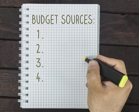 male hand is writing budget sources on a notepad on a wooden table Stock Photo