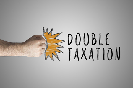 Double taxation concept. Punching Fist on whiteboard