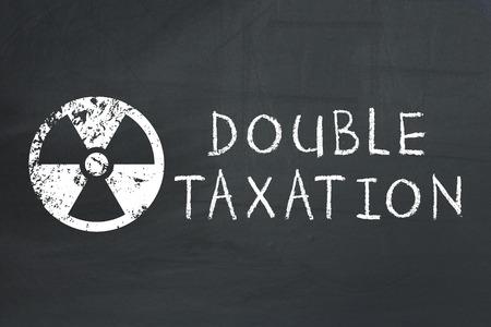 Toxic tax. Double taxation concept. on blackboard
