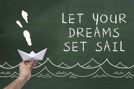 引用と黒い黒板に対して紙の船を持っている人間の手:あなたの夢は帆を設定してみましょう