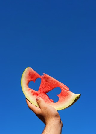 Male holding slice of watermelon heart cut towards the sky. Close up red juicy watermelon against the blue sky. Copy space.