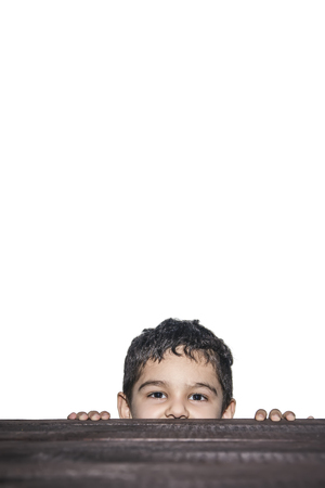 A boy spying over the wooden table. Cute young mixed race 4-5 years old boy boy looking over a wooden desk, white background with copy space